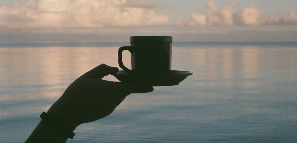 coffee cup in hand over water