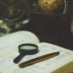 magnifying glass and pen on book in front of globes