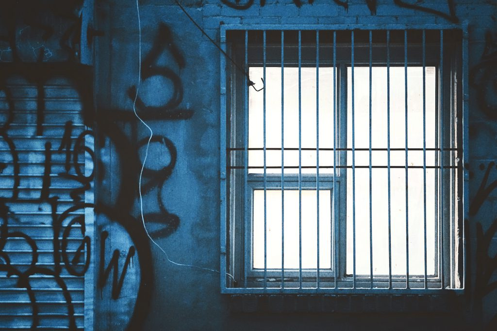 decorative image: graffiti on blue wall, window with bars