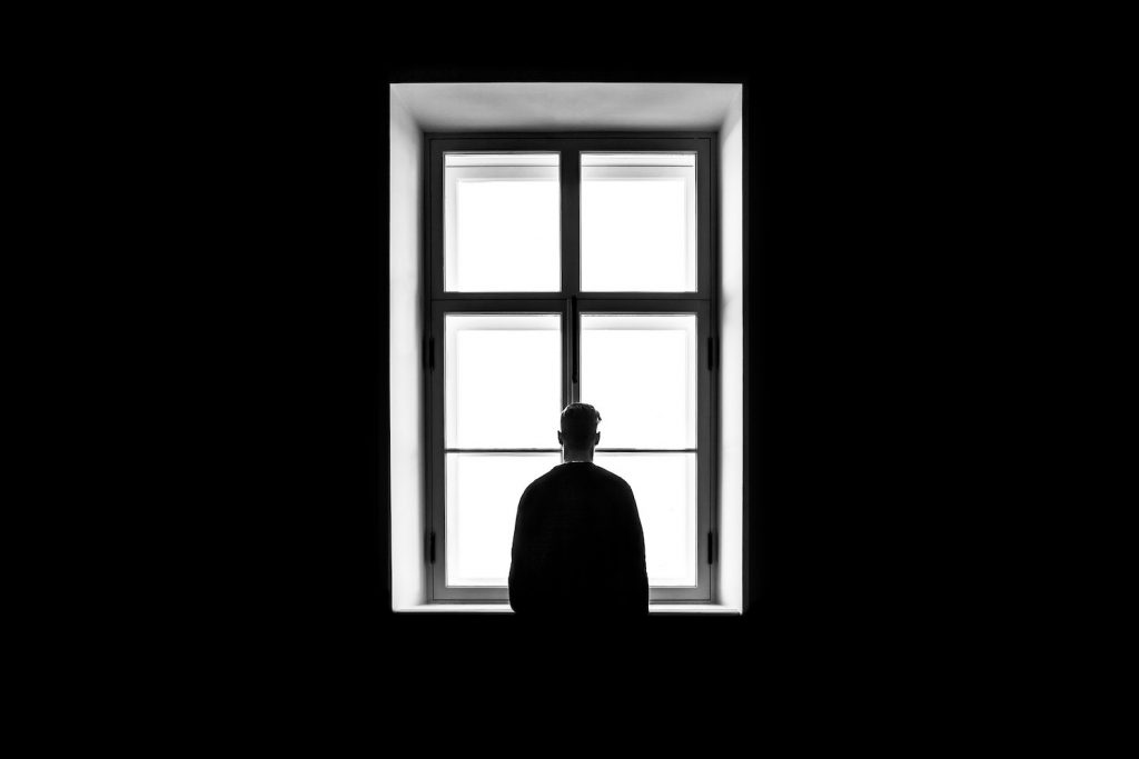 decorative image: figure looking out window, black and white