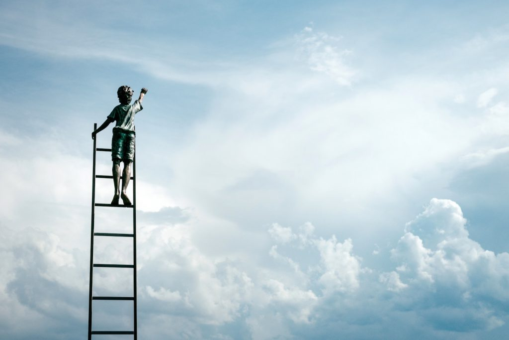 decorative image: boy on ladder reaching for clouds