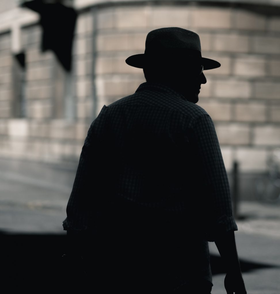 deco image: man with hat in shadow