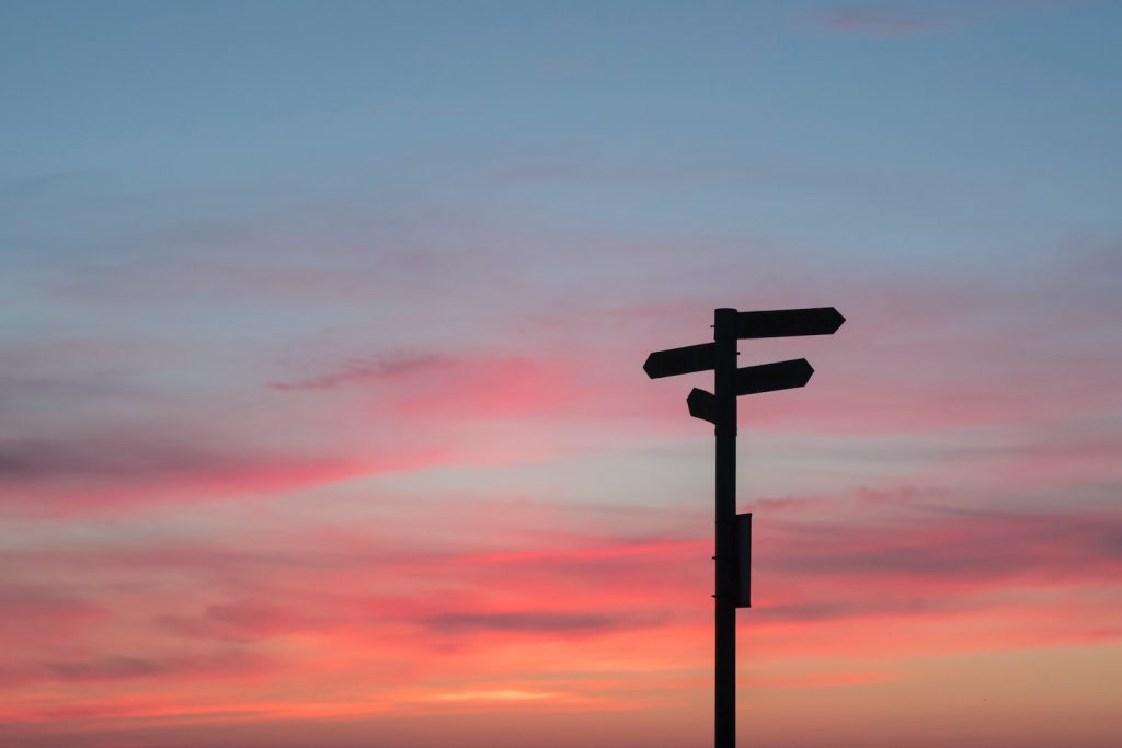 deco image: road sign again sunset sky