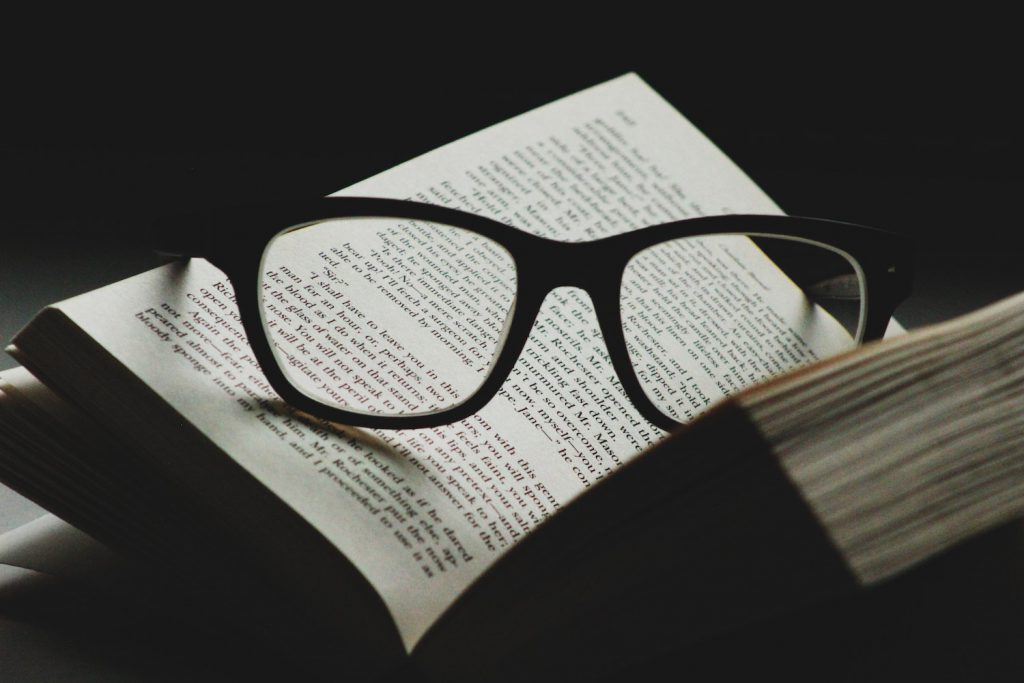 decorative image: glasses and books